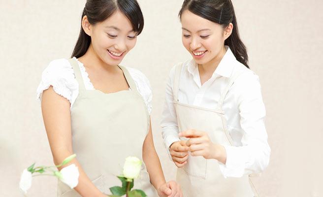 お花の生け方を教えてもらっている女性