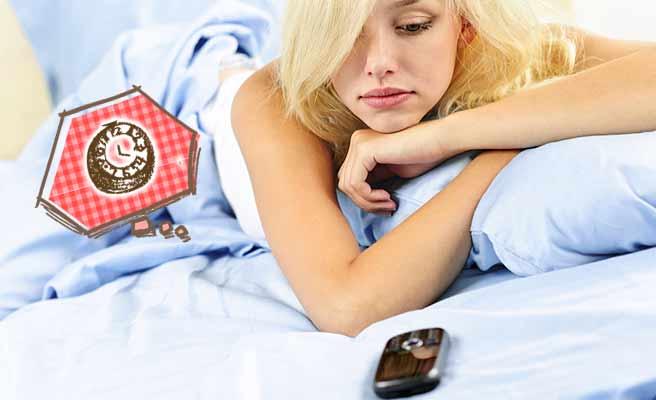 ベッドの上でスマホをじっと見つめる女性