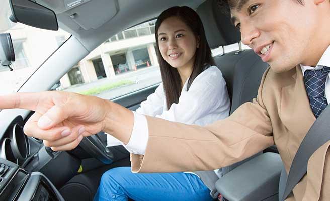 運転教習を受ける女性と指示する教官