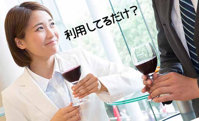 ワイングラスを持って立ちながら男性と会話する女性