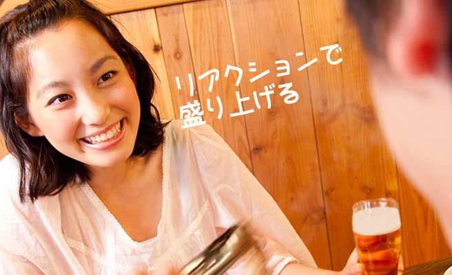 ビールジョッキを持ちながら笑顔で答える女性