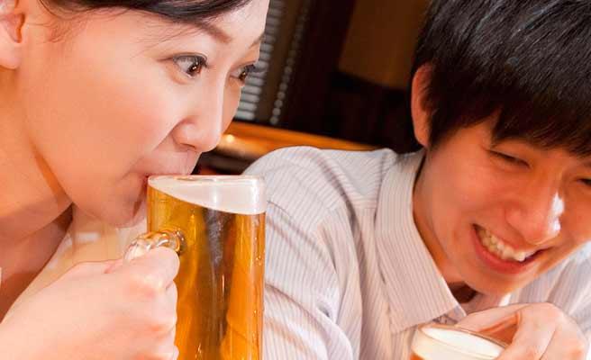 ビールをグイ飲みする女性と隣の席で笑う男性