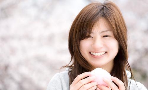 桜を背景に微笑む女性