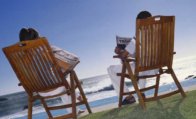 イスに座って海の景色を見るカップル