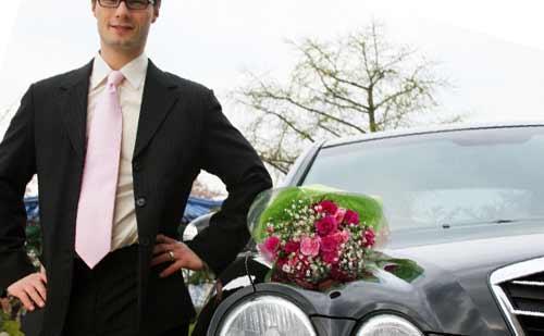車に花束を乗せこちらを見る男性