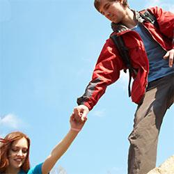 恋人の山登りを手伝う男性
