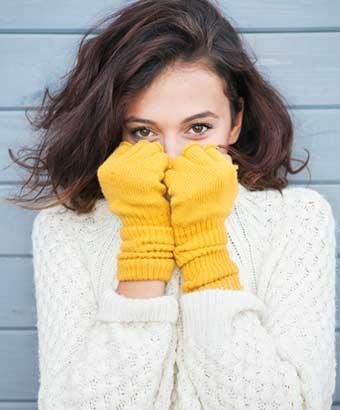 ニットのセーターと手袋の女性
