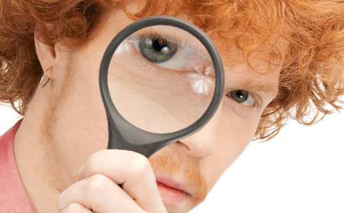 虫眼鏡でこちらを除く男性