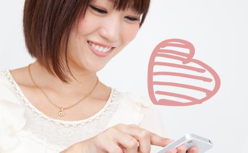 笑顔でスマフォを操作する女性