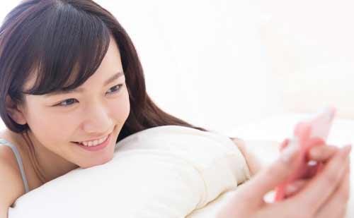 寝ながらスマフォをいじる女性