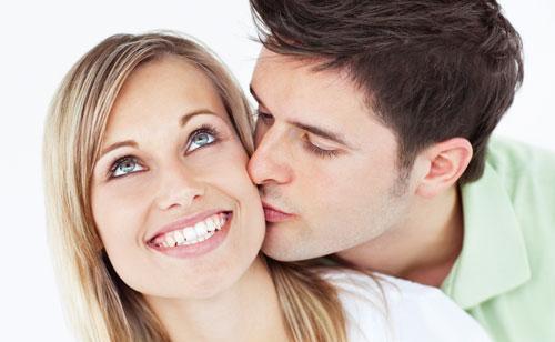 男性に後ろから抱きしめられホッペにキスもされて笑顔の女性