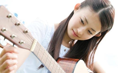 アコースティックギターのチューニングをする女性