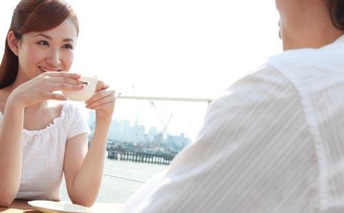 お茶を飲みながら笑顔で話す女性