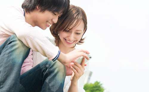 スマートフォンを一緒に眺めるカップル
