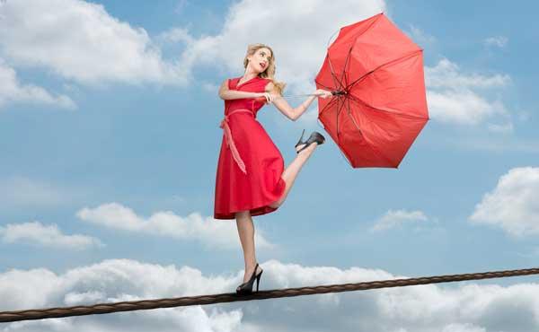 傘を持って綱渡りする女性