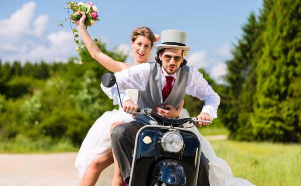 結婚衣装でバイクに乗るカップル