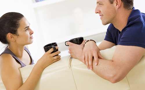コーヒーを飲みながらお互いを見つめ合う男性と女性