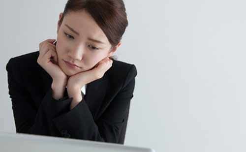 パソコンに向かい考え込む女性