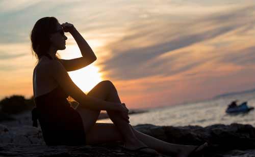 海で一人で遠くを眺める女性