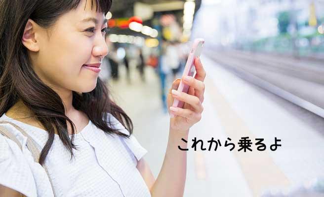 ホームで電車を待ちながらメールする女性