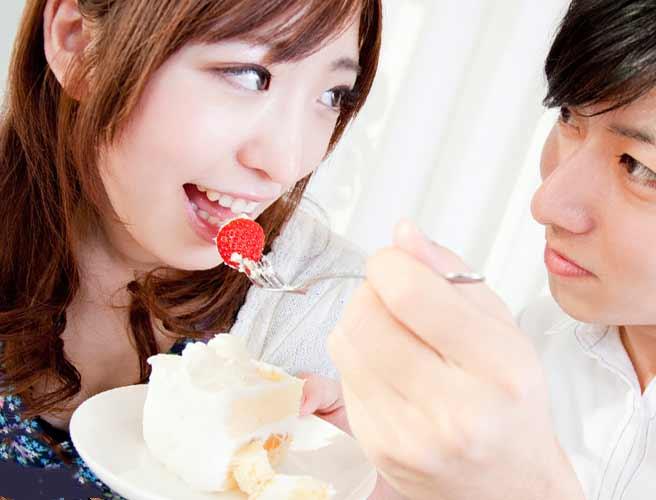 彼氏にケーキを食べさせてもらう女性