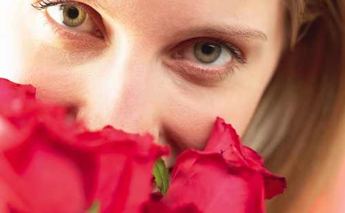 赤いバラを持ってこちらをみる女性