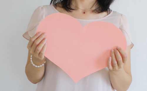 ピンクのハートマークを持つ女性