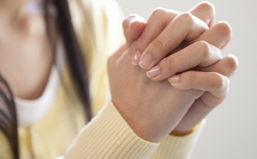 両手を組んで祈る女性