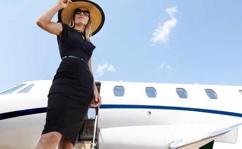 飛行機から降りて上を向く女性
