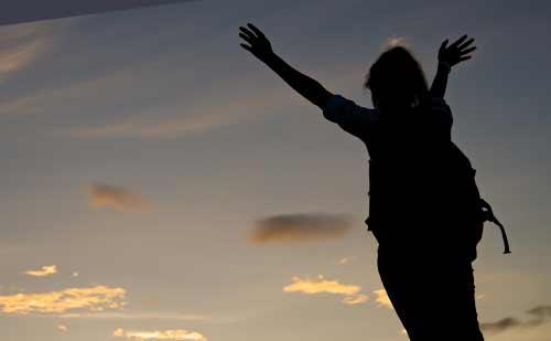 夕日に向かって手を上げる女性