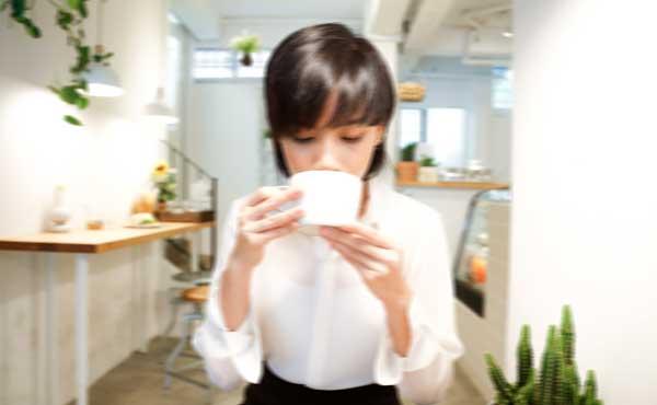 震えながらコーヒーを飲む女性
