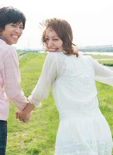 笑いながら手をつなぐカップル