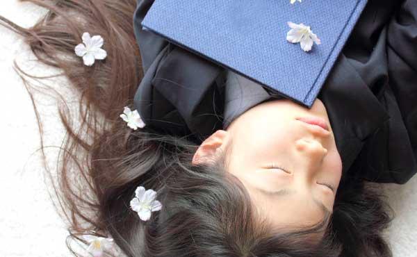 好きな他人のことを思いながら卒業アルバムを抱きしめる女子学生