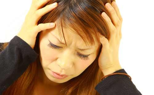 深刻な表情で頭を抱える女性