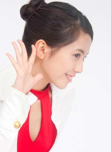 耳に手を当て聞こうとしている女性