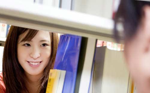 本棚の隙間から笑顔で男性を見つめる女性