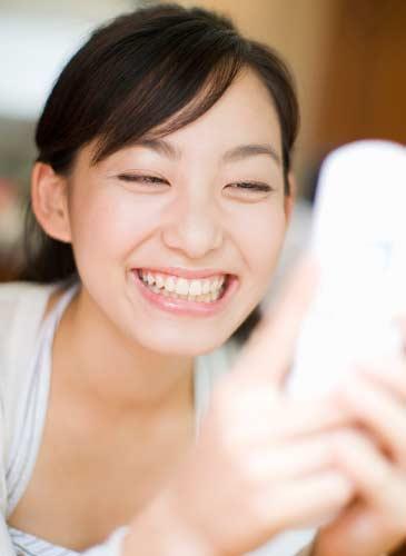 笑顔でメールをする女性