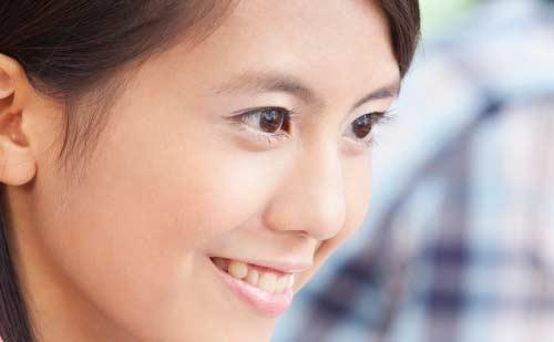 笑顔で遠くを見つめる女性
