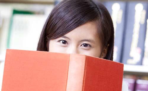 本の隙間から視線をおくる女性
