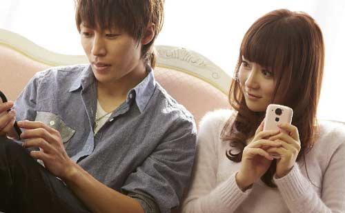 スマートフォンをいじりながら会話するカップル