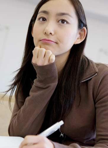 ノートを書きながら考える女性