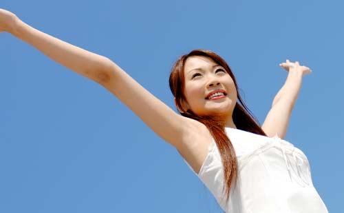 青空の下で両手を大きく広げる女性