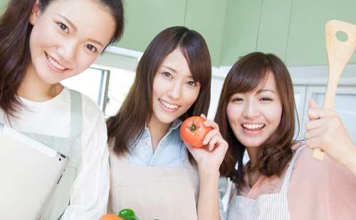 楽しそうに友達同士で料理をする女性