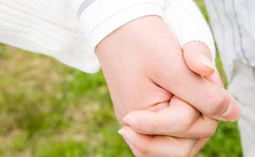 両手を握りしめる男女