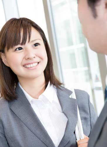 笑顔で男性と話すスーツ姿の女性