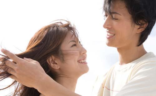 笑顔の女性の髪の毛を触る男性
