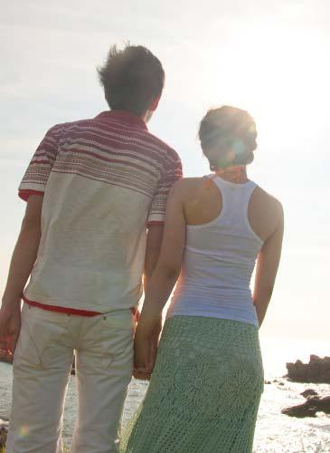 手を握り遠くを見つめるカップル