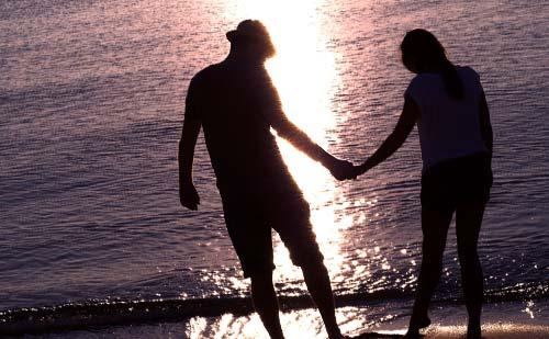 浪打際で手をつなぐカップル