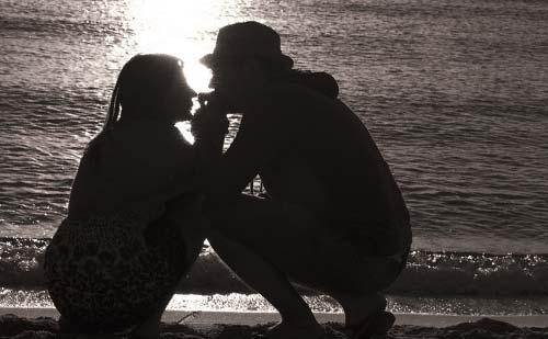 夕暮れの砂浜で近づくカップル