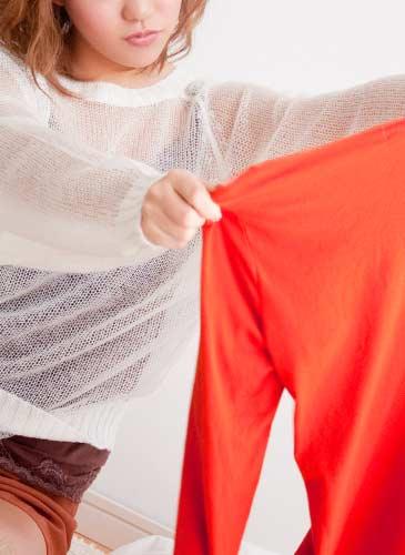 赤い服を手に取り悩んでいる女性